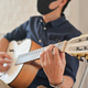 A young man wearing a mask playing guitar at home,Stay at home,Work from home. - PhotoDune Item for Sale
