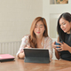 Two young female students with coffee are using laptop to study online at home. - PhotoDune Item for Sale