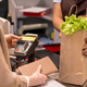 Hands of young cashier on paperbag with fresh groceries in front of buyer - PhotoDune Item for Sale