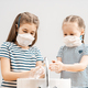 Girls are wearing face masks and washing their hands. - PhotoDune Item for Sale