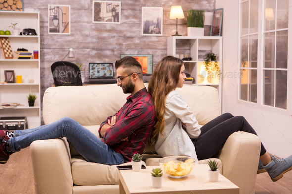 Couple sitting back to back on the couch ignoring each other - Stock Photo - Images