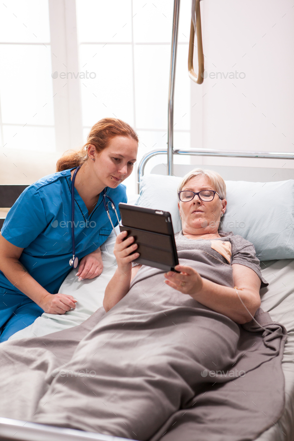 Young doctor and senior woman in nursing home - Stock Photo - Images