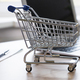 Mini empty shop cart trolley over a laptop computer on wood table background - PhotoDune Item for Sale