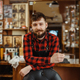 Barber with razor poses at the chair, barbershop - PhotoDune Item for Sale