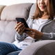 Young woman sitting on sofa at living room and using cell phone at home - PhotoDune Item for Sale