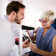 Senior woman taking an eyesight test examination at an optician clinic - PhotoDune Item for Sale
