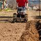 Gardener cultivate ground soil with tiller tractor or rototiller, cutivator - PhotoDune Item for Sale