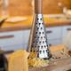 A piece of cheese on a wooden board next to an iron grater - PhotoDune Item for Sale