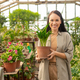 Pretty woman with potted plant in hothouse - PhotoDune Item for Sale