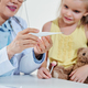 Pediatrician showing thermometer to girl - PhotoDune Item for Sale