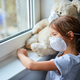 Little girl holding and hugging teddy bear in mask near the window. - PhotoDune Item for Sale