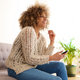 beautiful young african american woman sitting at home with mobile phone - PhotoDune Item for Sale