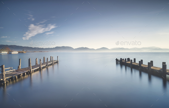 Two Wooden pier or jetty at sunset and sky reflection on water. Versilia Tuscany, Italy - Stock Photo - Images