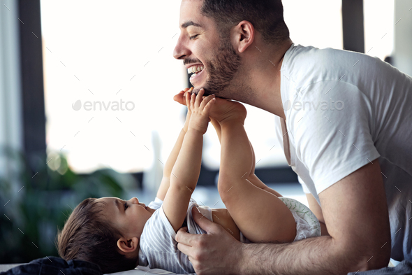 Smiling young father has fun with little baby while changing his nappy at home. - Stock Photo - Images