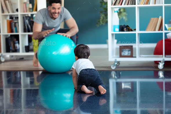 Handsome young father with his baby playing together and having fun with the ball at home. - Stock Photo - Images