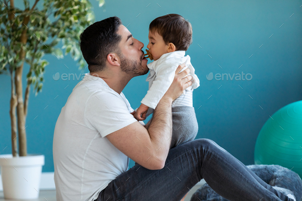 Handsome young father with his baby playing together and having fun at home. - Stock Photo - Images