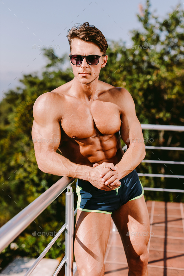 Fashion Portrait Of A Muscular Man posing shirtless in swim trunks and sunglasses - Stock Photo - Images