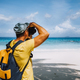 Male photograph with camera on paradise white sand tropical beach with turquoise blue ocean lagoon - PhotoDune Item for Sale