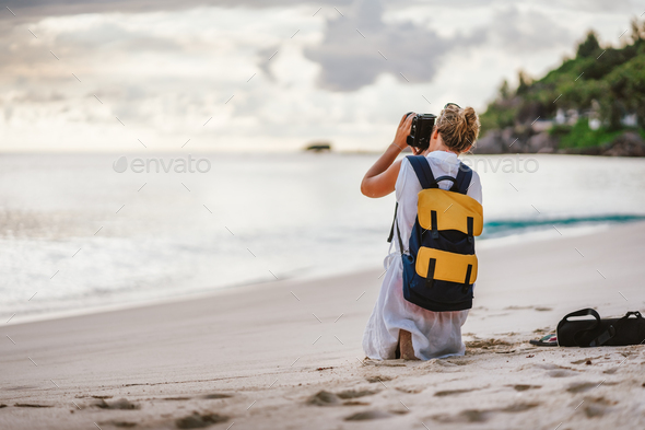Travel tourist female photograph sunset at tropical beach. Recreation hobby summer vacation
