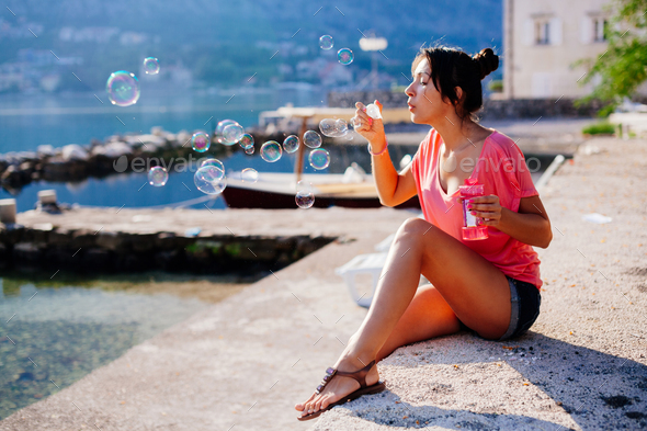 girl blow bubbles on beach - Stock Photo - Images