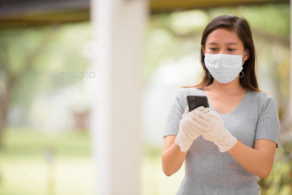 Young Asian woman using phone with mask and gloves - Stock Photo - Images
