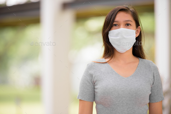 Young Asian woman wearing mask for protection from corona virus outbreak outdoors - Stock Photo - Images