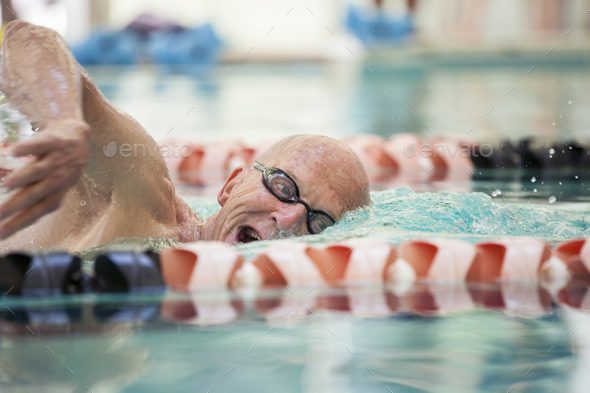 Close up shot of man in his mid 70s swimming laps in a pool. - Stock Photo - Images
