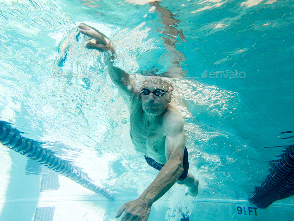 Athletic senior man in his mid 70s swimming laps, view from underwater. - Stock Photo - Images