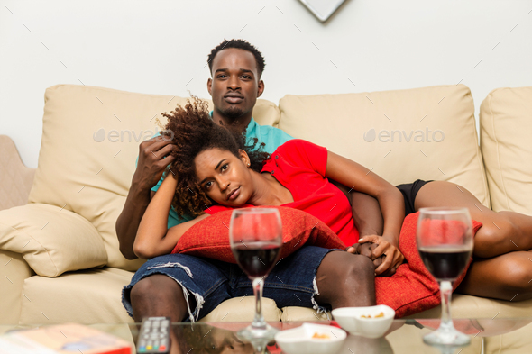 Black African American couple watching tv in the living room - Stock Photo - Images