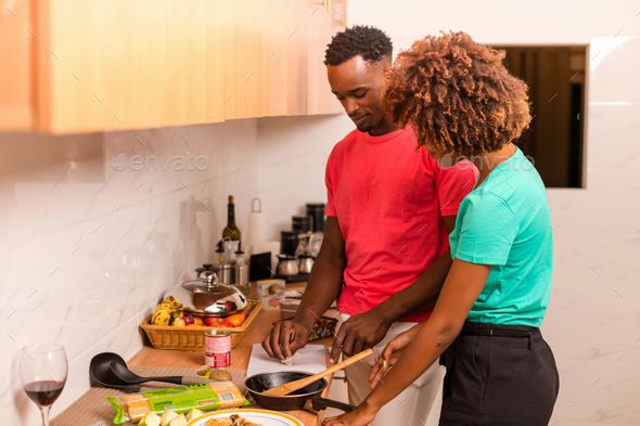 Black African American couple preparing food in the kitchen - Stock Photo - Images