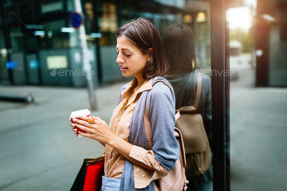 Happy young woman drinking take away coffee and walking with bags after shopping in city - Stock Photo - Images