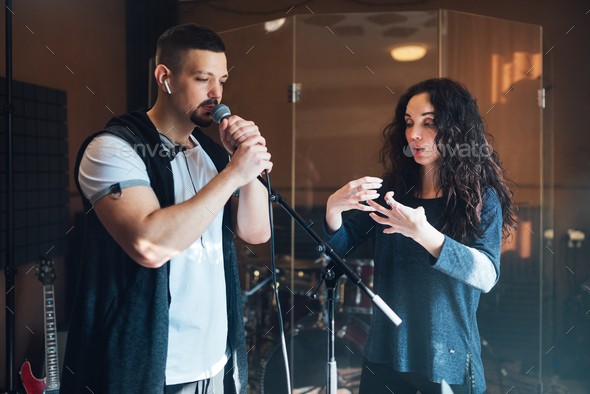 Musical teacher coaching a young male vocalist - Stock Photo - Images