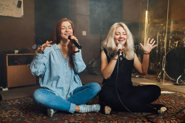 Two young woman sitting singing a duet - Stock Photo - Images