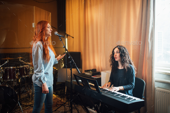 student girl sings in a vocal lesson to accompaniment of a teacher on an electronic keyboard - Stock Photo - Images