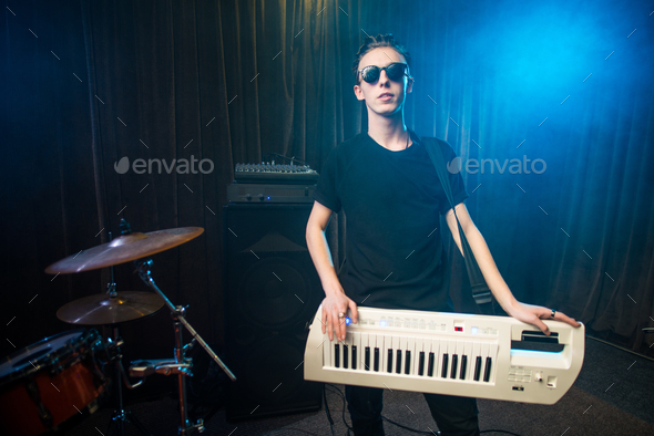 Man in sunglasses playing on electronic keyboard - Stock Photo - Images