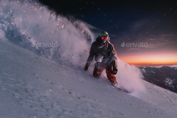 night skating snowboarder brakes spraying snow on freeride slope under starry sky and sunset light - Stock Photo - Images