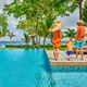 Family of three by poolside. Resort swimming pool at Seychelles. - PhotoDune Item for Sale
