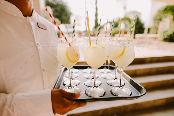 waiter holding glasses with cocktail hot summer - Stock Photo - Images