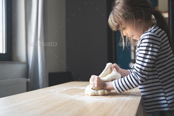 little Caucasian girl working the dough on a wood cutting board - Stock Photo - Images