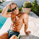 Sexy shirtless man in swim trunks with athletic body posing near pool - PhotoDune Item for Sale