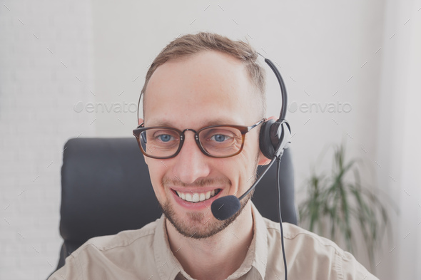 Young man with headset for online communication. Support or customer service worker - Stock Photo - Images