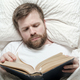 Attractive bearded man reading a book while lying in bed. Education concept. Top view. - PhotoDune Item for Sale