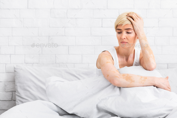 Depressed middle aged woman sitting on bed at home - Stock Photo - Images