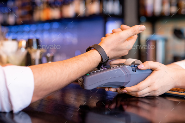 Young client with smartwatch keeping his wrist over payment machine - Stock Photo - Images