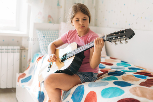 Cute tween girl in pink t-shirt play guitar sit on bed - Stock Photo - Images