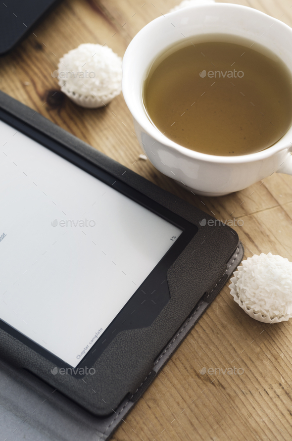 E-book reader and tea cup - Stock Photo - Images