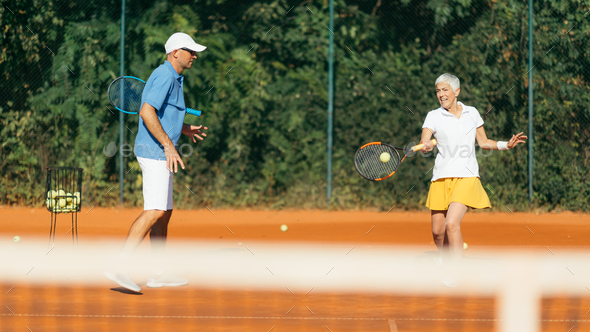 Tennis instructor with senior woman, tennis training lesson