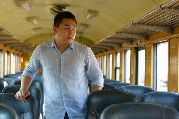 Young overweight Asian tourist man looking through window inside the train