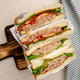 Flat lay view at wrapped Tuna sandwiches with lettuce tomatoes pickles and onions - PhotoDune Item for Sale