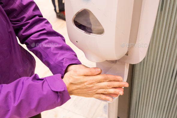 Person cleaning hand with anti-bacterial diinfectant sanitizer in public mall - Stock Photo - Images